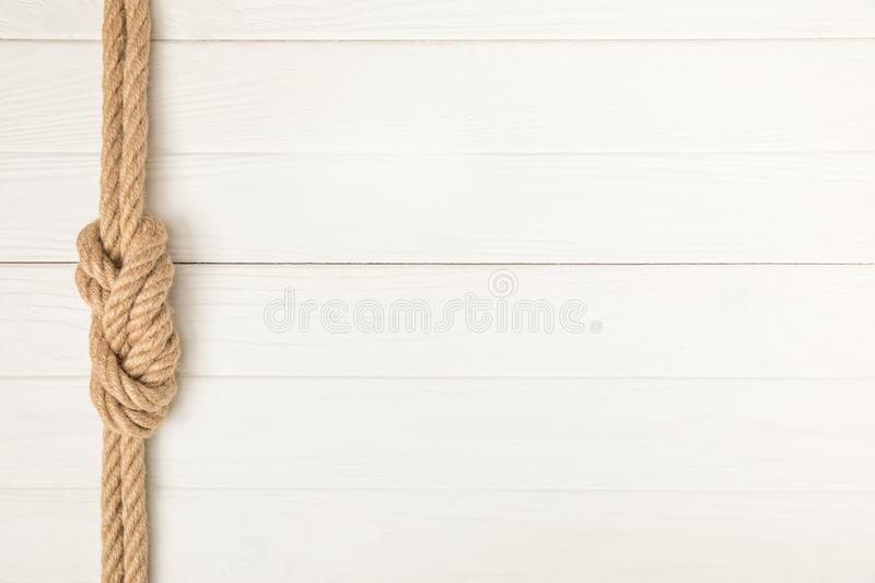 top view of brown nautical rope with knot on white wooden surface stock photo