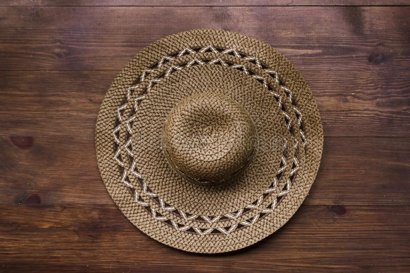 Top view of brown rustic straw hat on wooden background. Summer vacation rural concept. Close-up of accessory of clothing women royalty free stock images