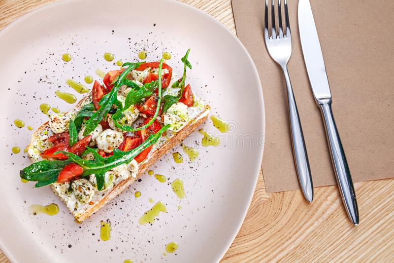 Top view on bruschetta with mozzarella, cherry tomatoes and arugula served on plate on wooden table. View from above on flat lay royalty free stock photos
