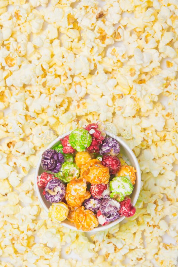 Top view, a bucket of sweet, multicolored popcorn, against the background of scattered flakes royalty free stock images
