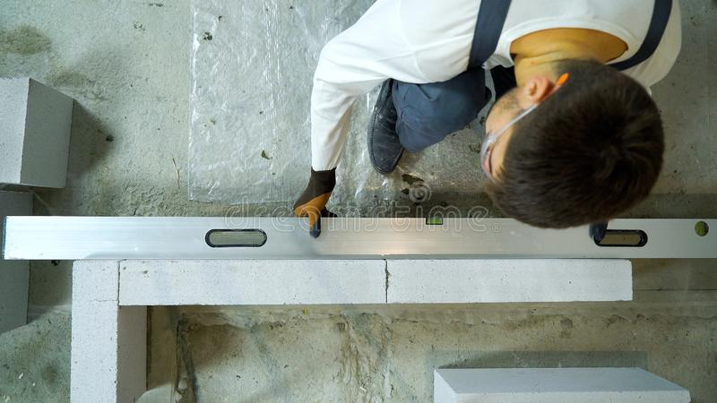 Top view of builder checking evenness of aerated concrete wall with spirit level. Construction worker building interior wall. house renovation, construction stock photo