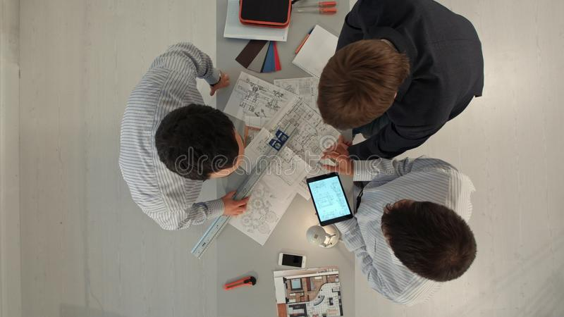 Top view of Builders discussing blueprint indoors. Building, renovation, repair, teamwork and people concept stock images