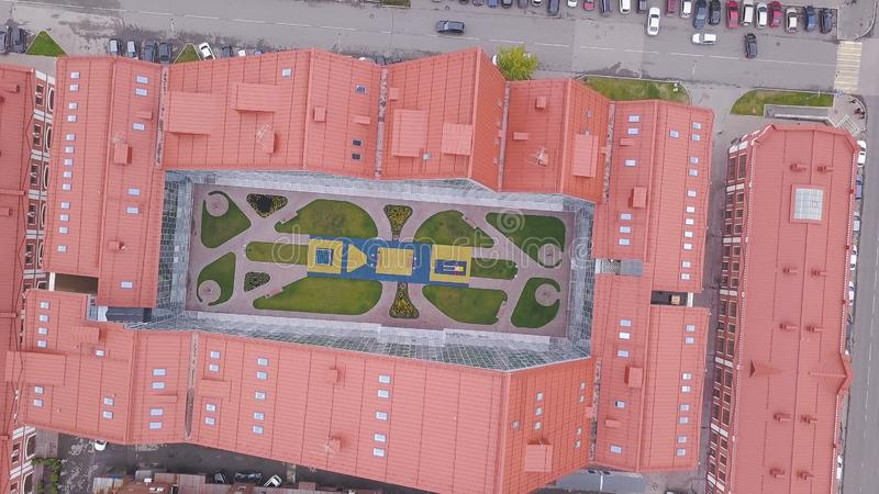 Top view of building with open space in center. Clip. Top view of U-shaped closed complex building with red roofs.  stock image