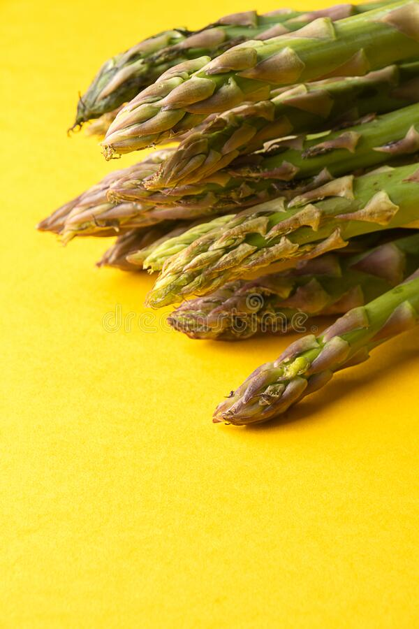Top view of bunch of green asparagus diagonally on yellow surface in vertical stock photo