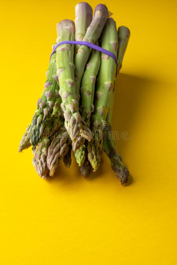 Top view of bunch of green asparagus tied with a purple rubber, on yellow surface in vertical stock photo