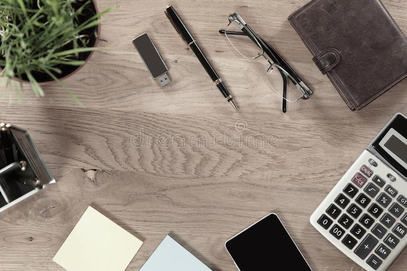 Top view.business background.calculator,mobile phone and other items on wooden table.  royalty free stock photography