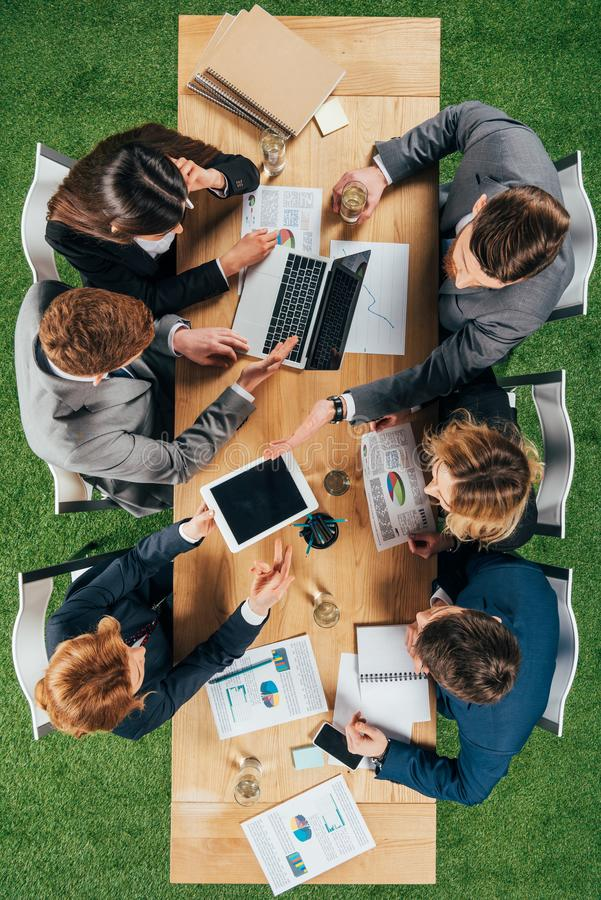 Top view of business colleagues working at table with laptop smartphone and tablet royalty free stock image