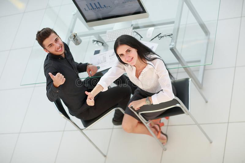 Top view. business couple sitting at Desk and showing thumbs up royalty free stock images