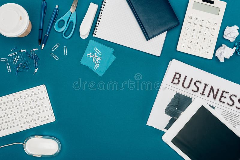 top view of business newspaper, digital tablet, calculator and office supplies royalty free stock images