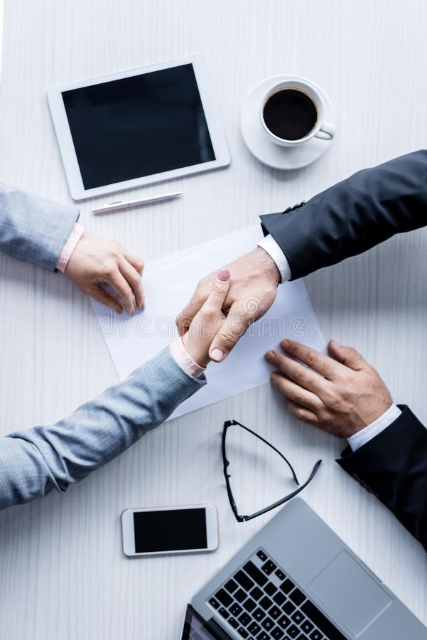 top view of business people shaking hands stock images