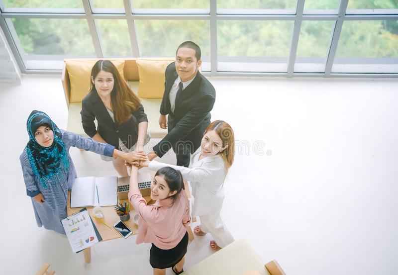 Top view of Business people in team stack hands together as unity and teamwork in office. young Asian businessman. And group togetherness collaboration stock photos