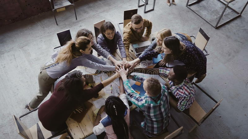 Top view of business team working at trendy loft office. Young mixed race group of people puts palm together on centre. royalty free stock photography