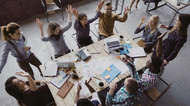 Top view of business team working at trendy loft office. Young mixed race group of people puts palm together on centre. royalty free stock images
