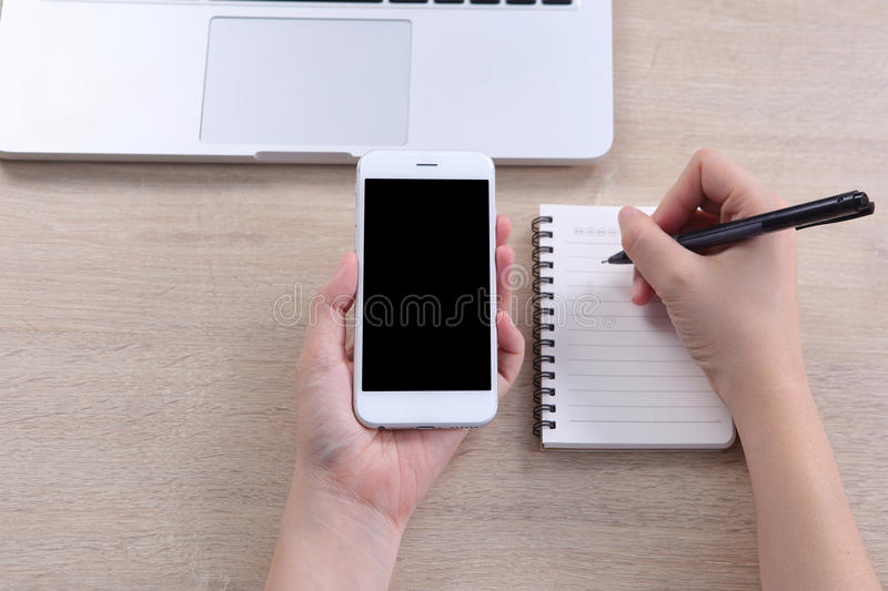 Top view business woman holding mockup smartphone with writing o. N a note book on wooden desk royalty free stock photo