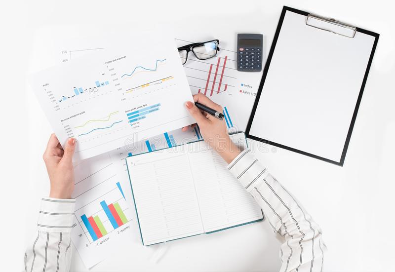 Top view of business woman`s hands analyzes the charts on white table royalty free stock image