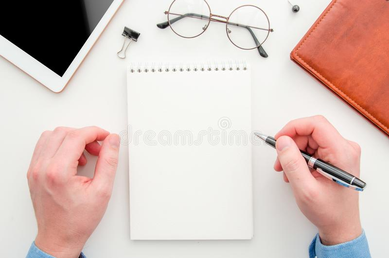 Top view businessman holding pen and taking notes at blank spiral notepad. Flat lay workspace with glasses, tablet and stock image