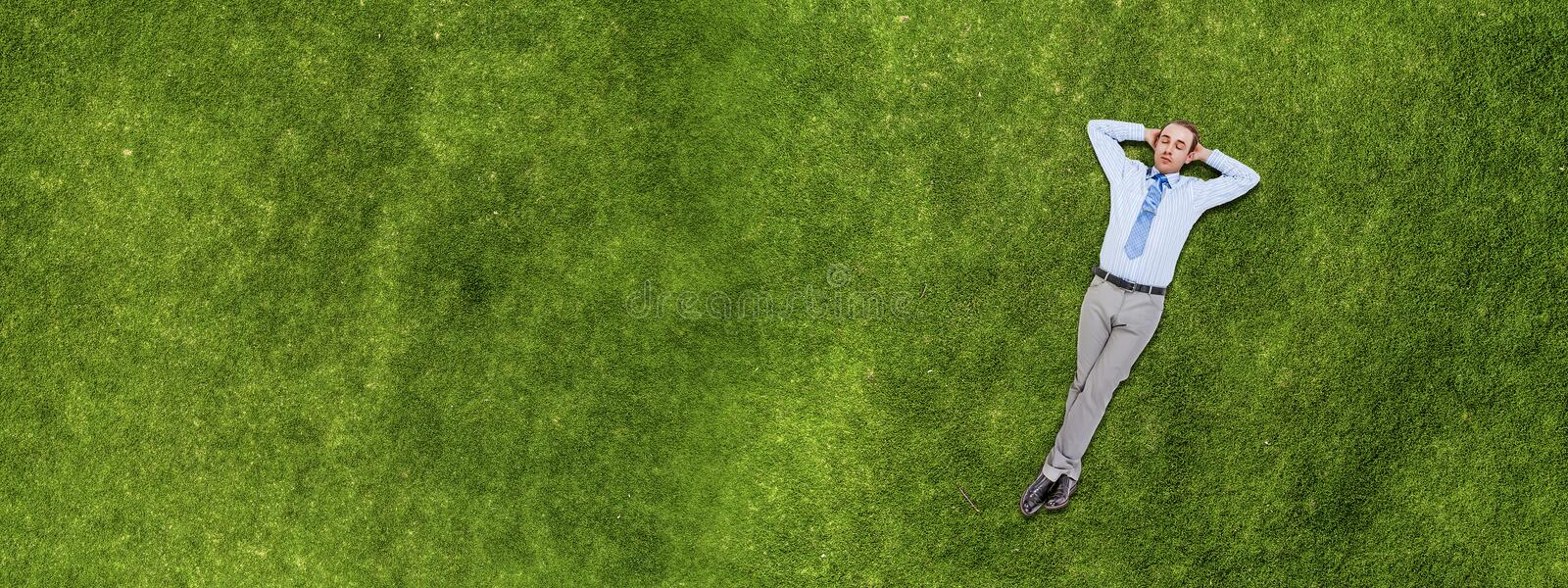 Relaxing businessman on grass stock image