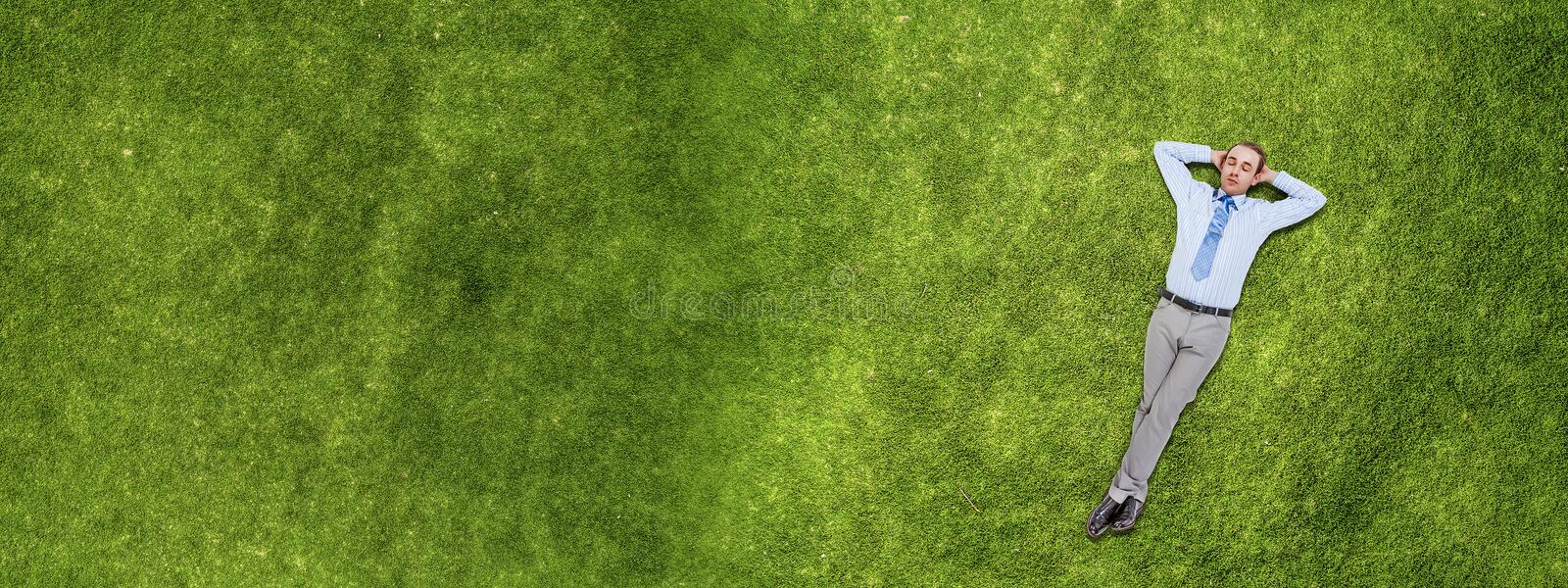Relaxing businessman on grass royalty free stock photo