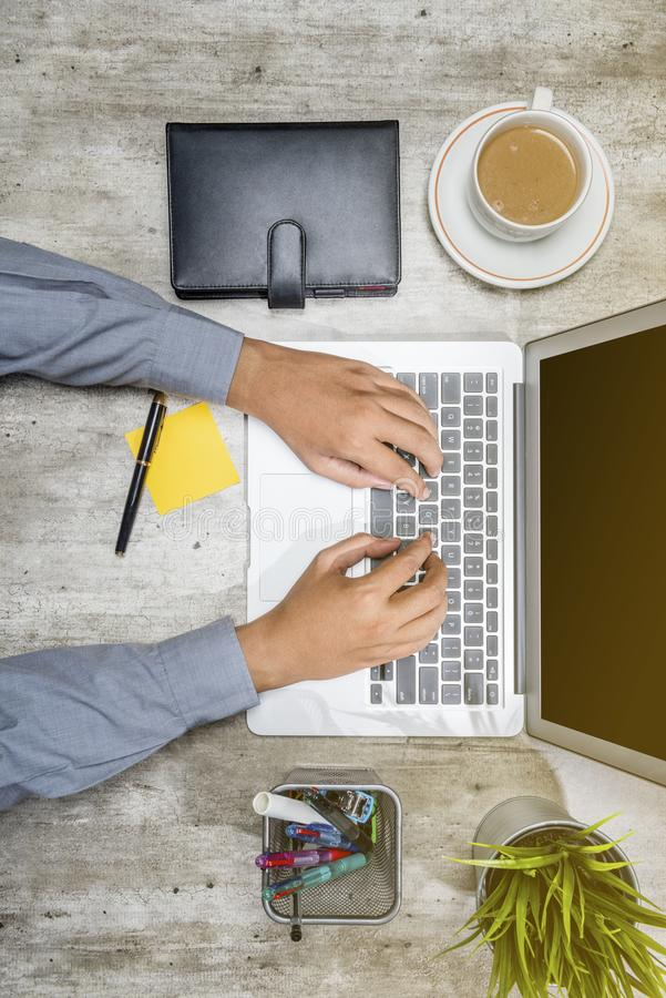 Top view of businessman working using laptop with coffee, potted plant, notebook, notes paper and business accessories royalty free stock photography