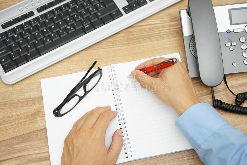 Top view of businessman writing a memo in notepad stock photos