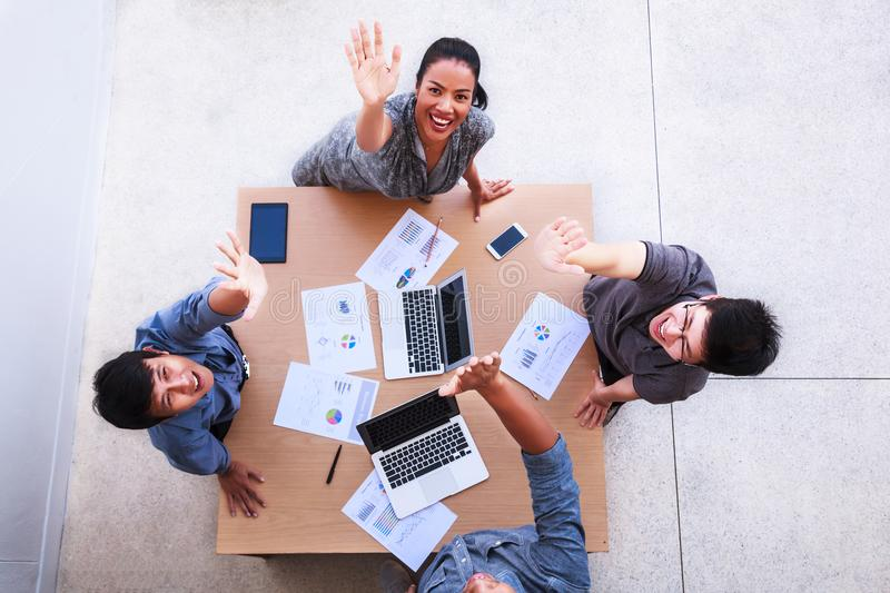 Top view of businessmen and businesswoman celebrate over table in a meeting with copy space at mobile office. Teamwork, diversity stock photography