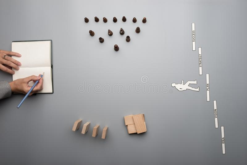 Top view of businesswoman creating her business vision. Writing on note pad with wooden blocks, chess pieces and words of achievement on gray desk royalty free stock photography