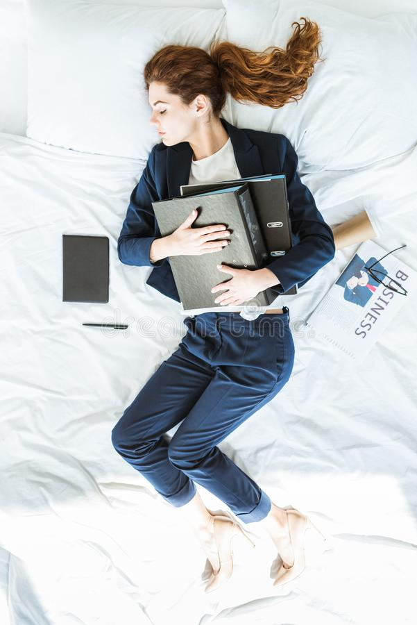 Top view of businesswoman in suit sleeping and holding folders. In bed stock photo