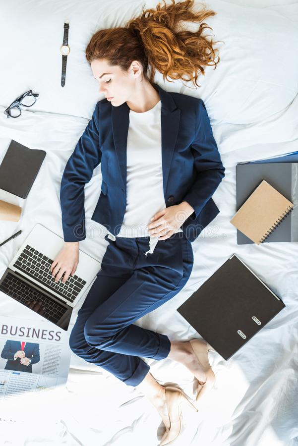 Top view of businesswoman in suit typing on laptop while lying in bed among folders. And documents stock images