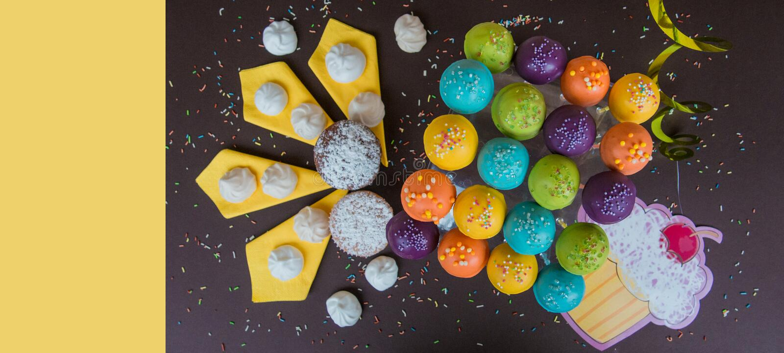 Top view of cake pops on a dark brown background with bright yellow copy space stock image