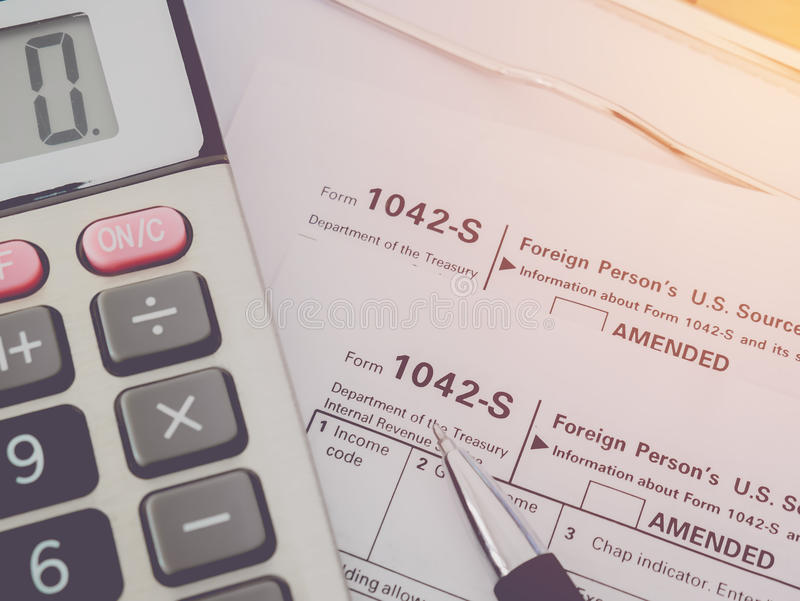 Top view calculator with pen on Tax Season. 1042 U.S. Individual Income Tax Return royalty free stock photography