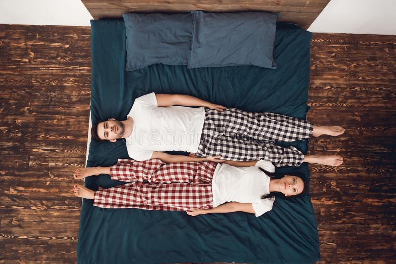 Top view. Calm young couple lies across bed perpendicular to each other. royalty free stock image