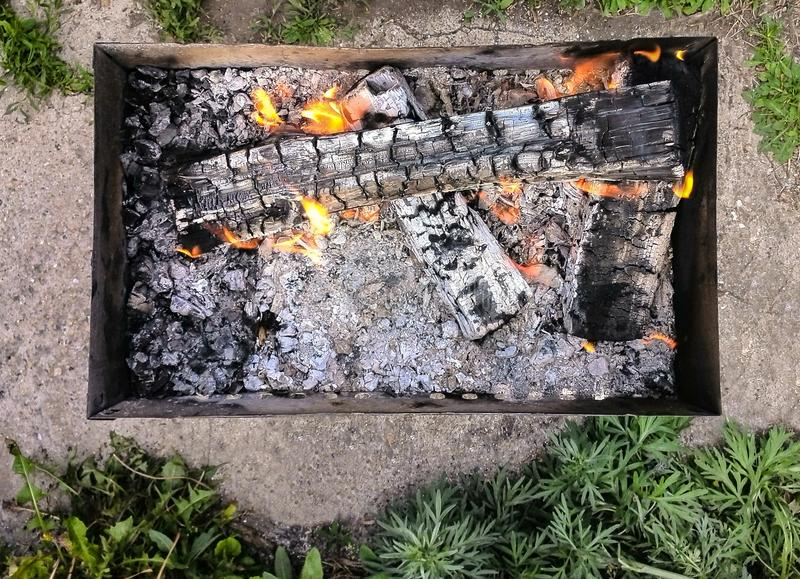 Top View Of A Camping Portable Charcoal Barbecue With Fire Flames, Green Grass Around royalty free stock image