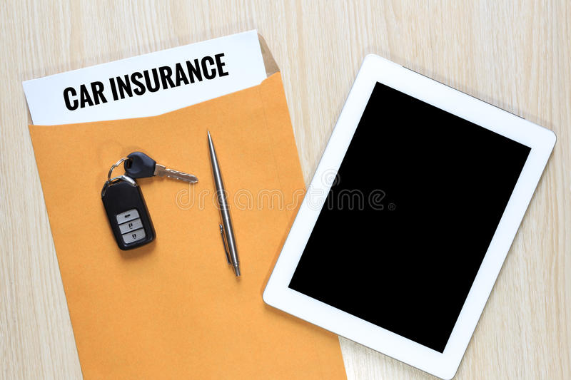 Top view of Car insurance in envelope with car remote key and ta. Blet royalty free stock photography
