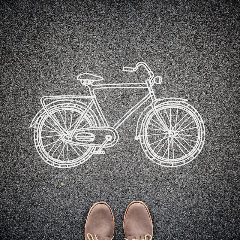 Top view of casual man's shoes and a sketched model of a bicycle on asphalt. A concept of environmental friendly way of travelling. In the city royalty free stock images