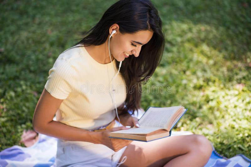 Top view of Caucasian brunette beautiful young smiling woman with earphones, listening to music and reading a book at the park. stock photos
