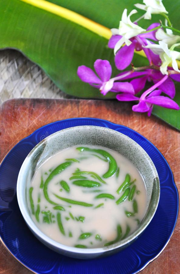 Top View of Cendol Bowl on Wooden Board. With orchid and banana leaf on background stock image