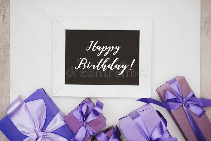 top view of chalkboard with happy birthday lettering and various gift boxes royalty free stock photo