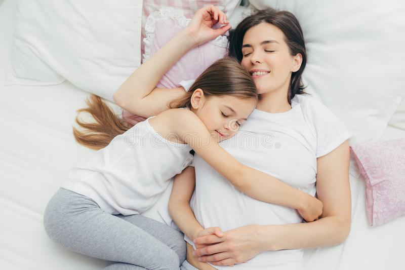 Top view of cheerful mother sleeps on white bed near her daughter who embraces mum with great love, shows good attitude, have royalty free stock images