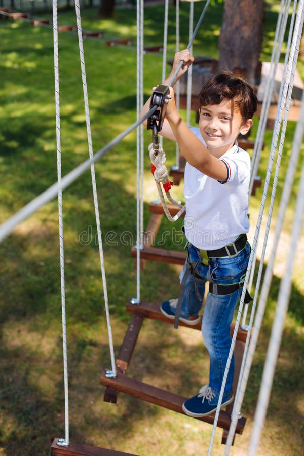 Top view of cheerful preteen boy climbing at rope park stock photo