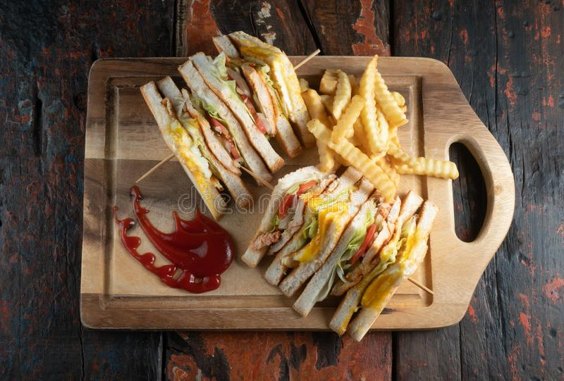 Chicken club sandwiches and french fries on rustic wooden table. Top view of chicken club sandwiches and french fries  on rustic wooden table stock image