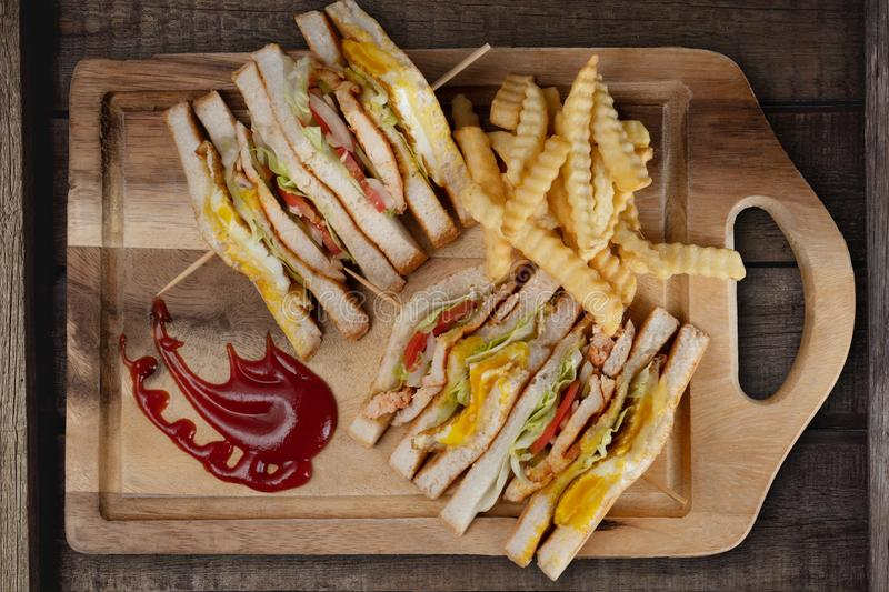 Top view of chicken club sandwiches and french fries on rustic wooden table stock photography