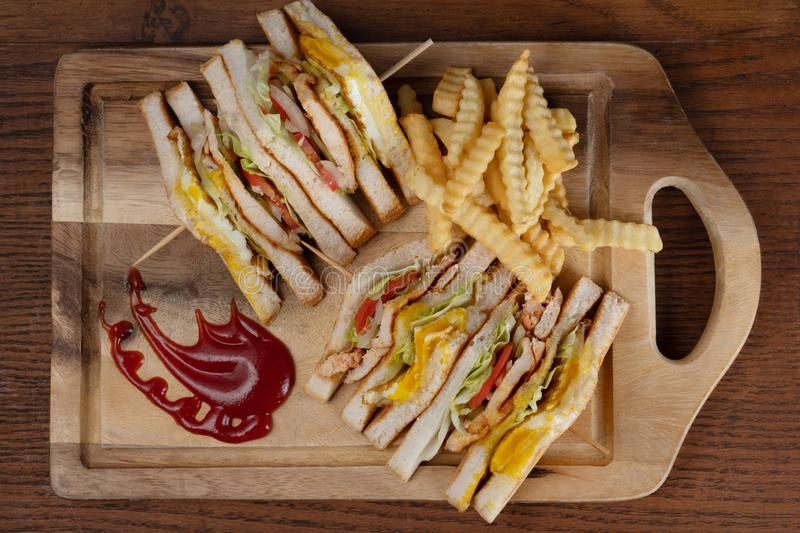 Chicken club sandwiches and french fries on wooden table. Top view of chicken club sandwiches and french fries  on wooden table royalty free stock photos