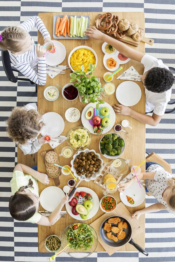 Top view on children eating healthy food at table during birthday party stock photography