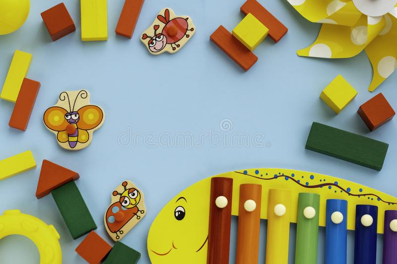 Top view on children`s educational and music games, frame from multicolored kids toys on light blue paper background. Wooden cubes, stars, circles, ladybag royalty free stock images