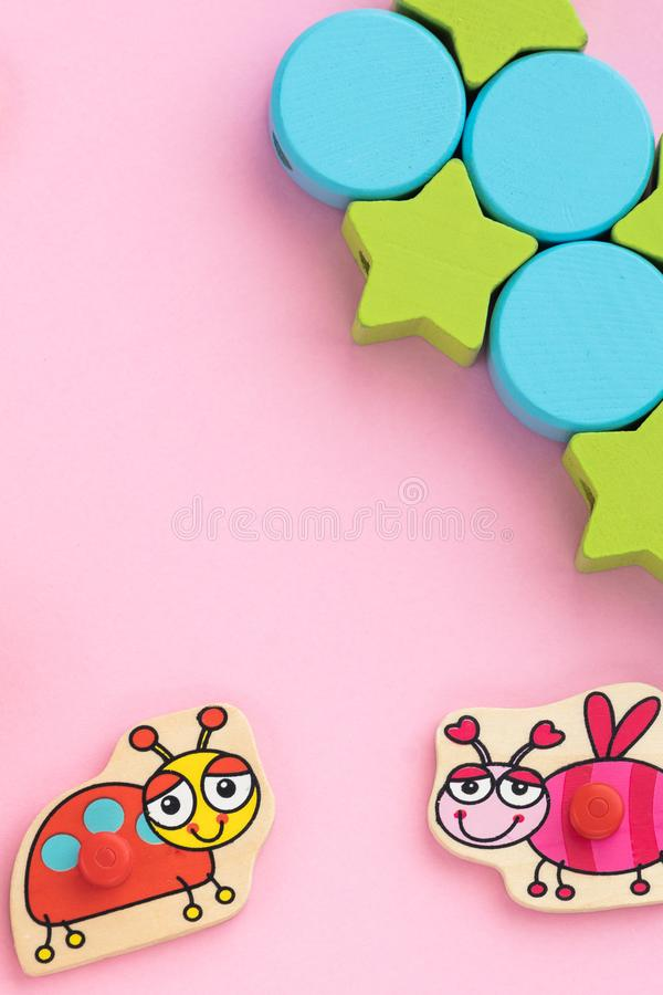 Top view on children`s educational toys, stars,circles on a pink background. Cute puzzle ladybug, bee. Flat lay, copy stock photo