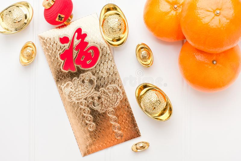 Top view Chinese New year golden envelope packet ang pow wit. H gold ingots and tangerine on white wood table top,Chinese Language on envelop mean Happiness and stock images