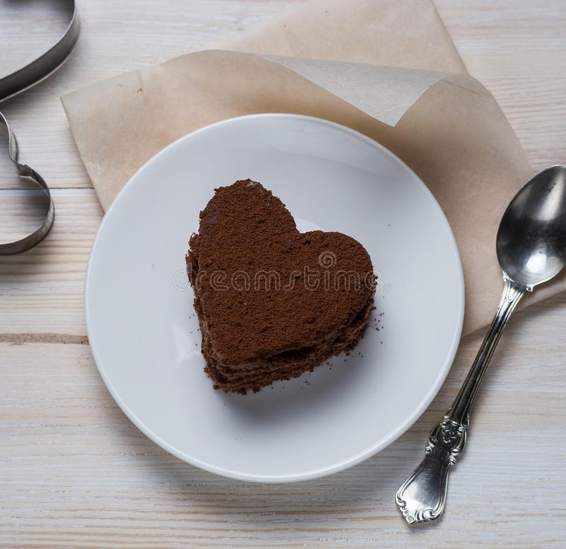 Top view of a chocolate heart-shaped dessert lying on a saucer next to a silver spoon and iron molds on a white wooden stock photography
