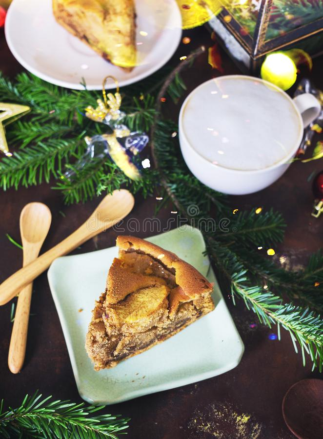 Top view Christmas dessert table: apple pie, hot capucino with tree branches and toys. New year stock image
