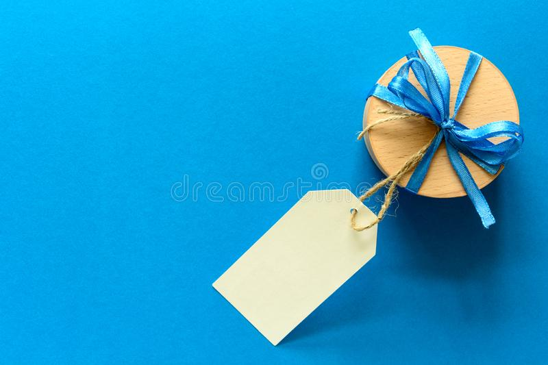 Top view on Christmas gift box decorated with ribbon on blue paper background. royalty free stock photo
