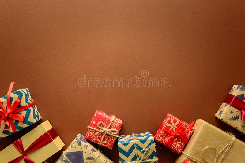 Top view on Christmas gifts wrapped in gift paper decorated with ribbon on brown paper background. royalty free stock photos